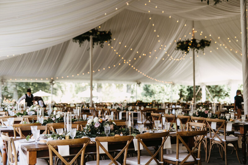 Beautiful romantic open-air white wedding reception tent filled with styled tables and lovely wooden chairs