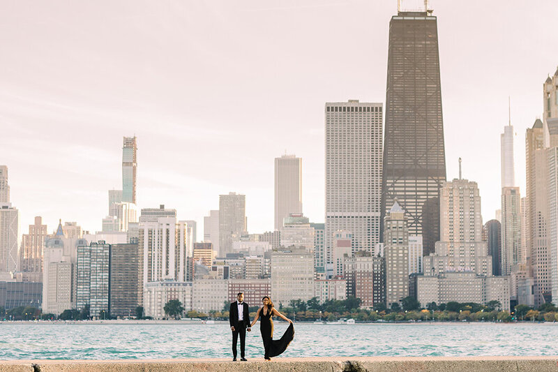 Couple pose in front of the Chicago skyline at North Avenue Beach for engagement photo.