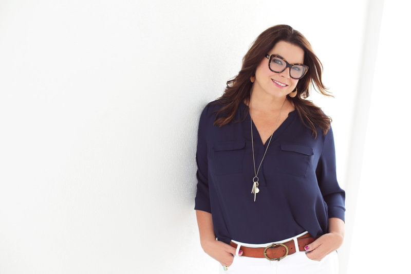 Photo of Glossible founder, Sonia Roselli, leaning against a wall in navy blouse and white pants