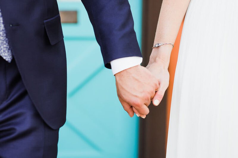 Close up of bride and groom holding hands in front of turquoise door on their wedding day