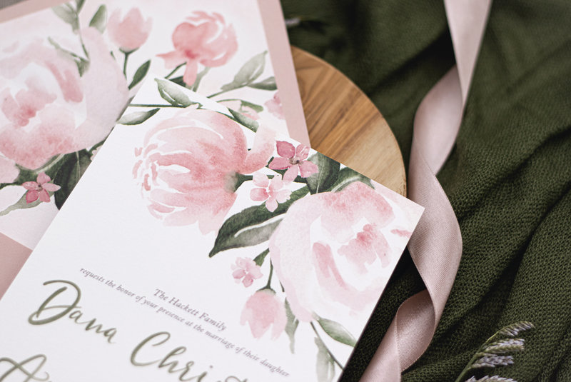 Detail shot of the watercolor peony floral on the top of the wedding invitation.