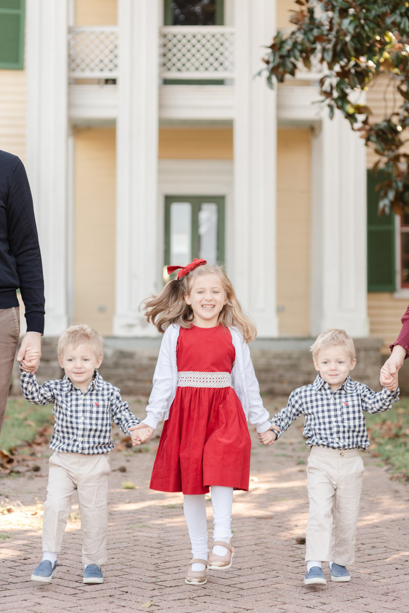 An older sister wearing a red dress is holding her two younger brothers hands on either side as they walk up to the camera smiling on a cold day in Nashville