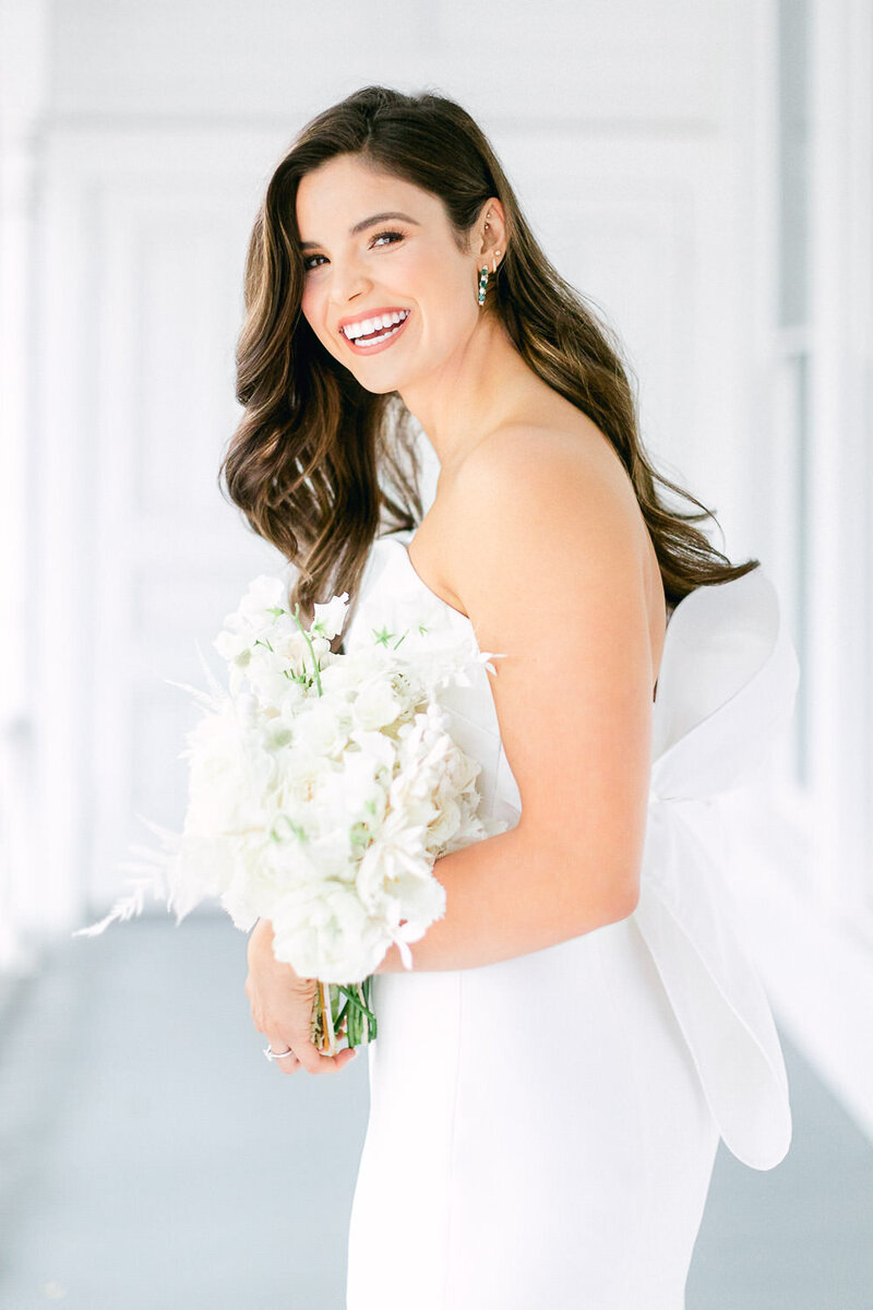Bride in strapless wedding dress  laughing while holding flower bouquet