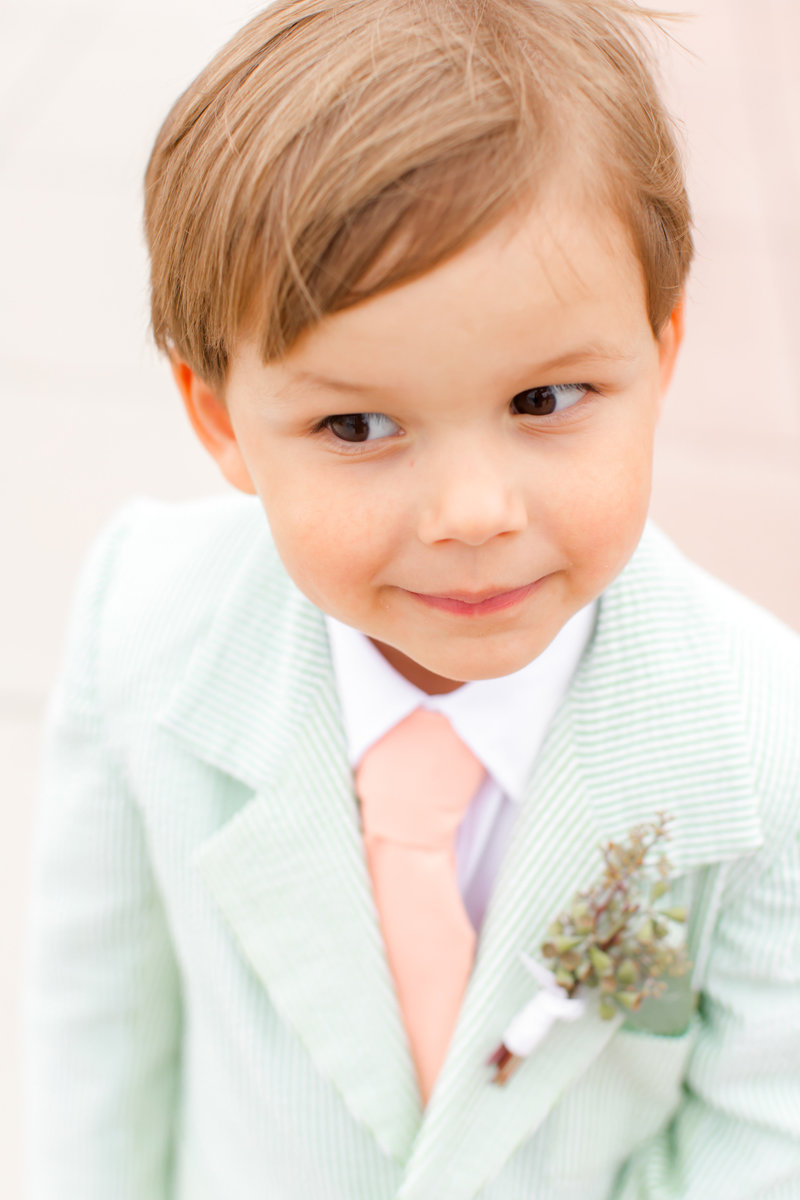 Ring bearer wearing seersucker suit in green