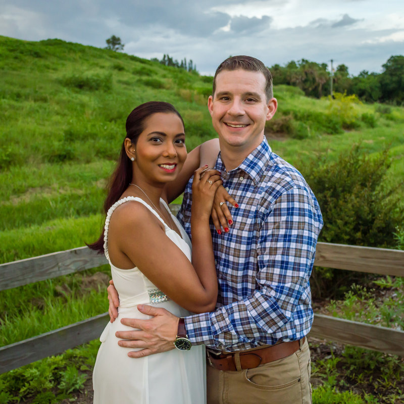 Engaged couple poses at a park in front of wooden fence