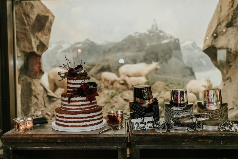 Wedding dessert table with naked cake and New Years Eve hats at this Natural History Museum wedding reception