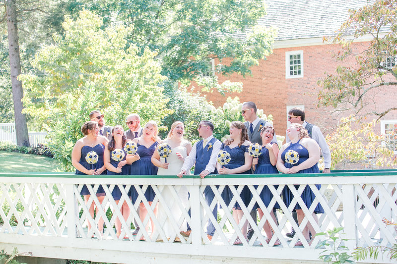 Bride, groom, and their bridal parties smile atop a white bridge holding bouquets