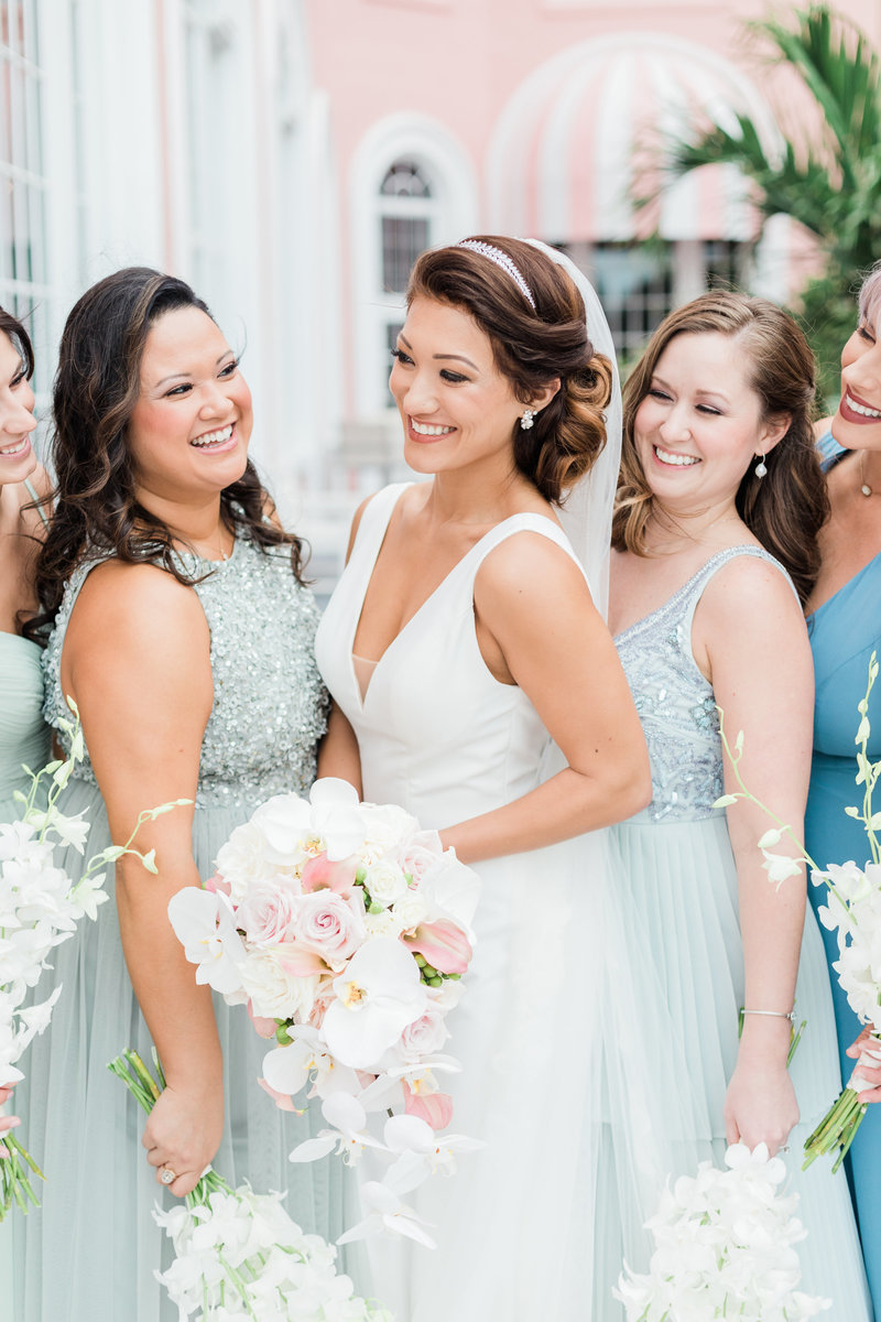 bride laughing with her bridesmaids on balcony of don cesar hotel in st petersburg florida by costola photography