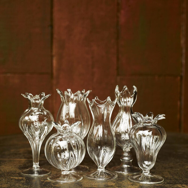 A selection of glass bud vases  against a wooden wall.
