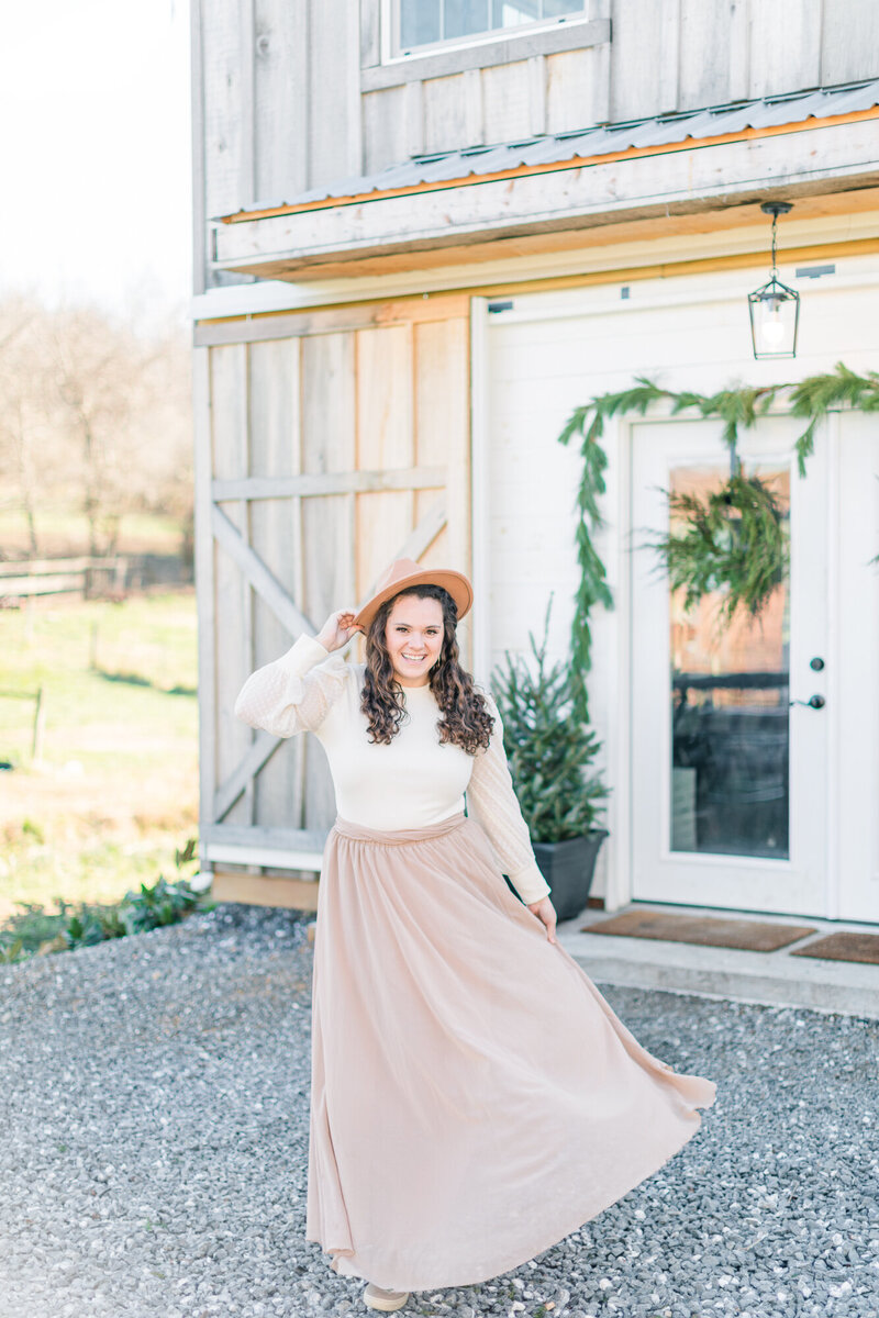 Woman wearing nude colored flowy skirt outside of Seasons Yield Farm. Ashley Eagleson, a local wedding photographer, posing for portrait.
