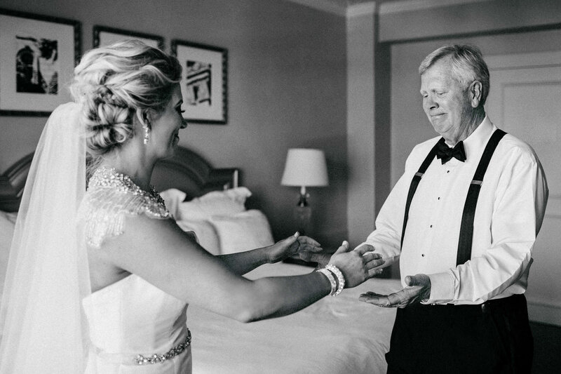 bride reaching hands out to emotional father in suspenders