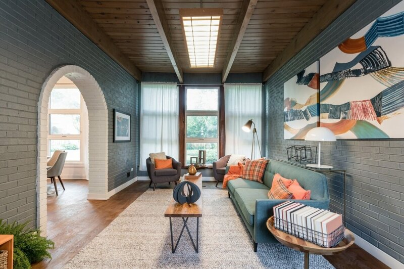 Blue and Teal Living Room blue walls wood coffee table grey side chair teal sofa orange pillows and throw blanket wood side table