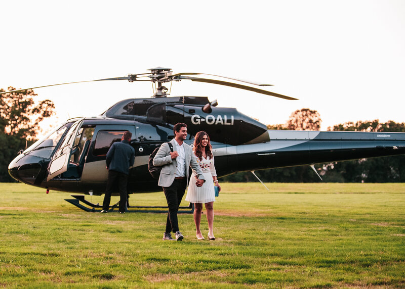 A smartly dressed couple walk away from a helicopter after getting engaged.