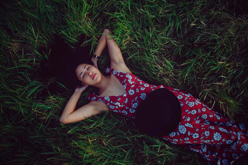 girl laying in tall grass with red dress