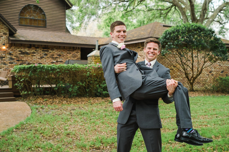 Groom's brother holds him like a baby to recreate family photo