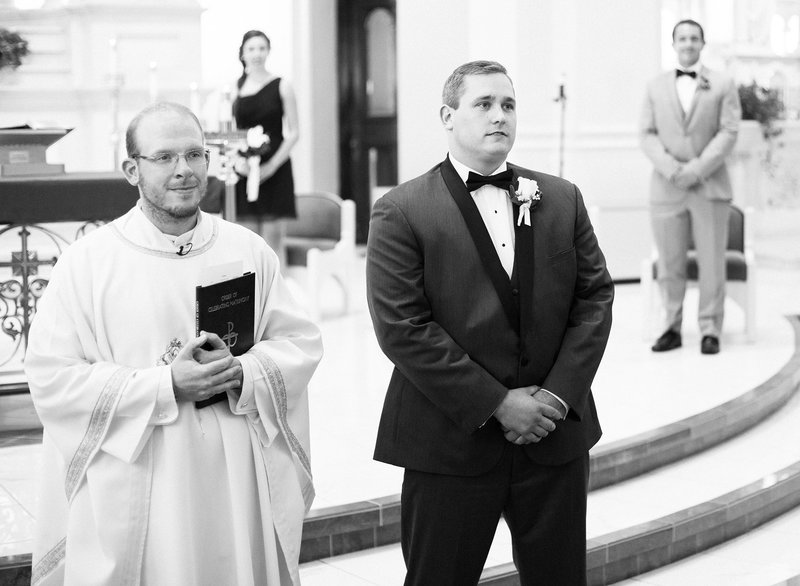 Groom and priest watch bride walk down the aisle at St. Patrick's Church wedding