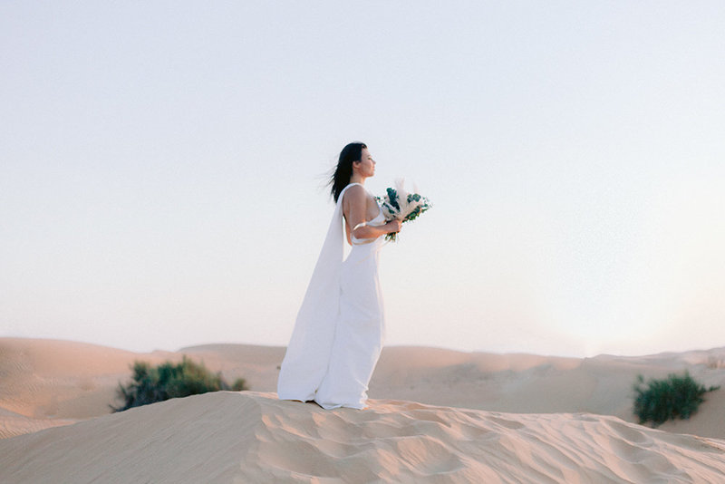 woman on a dune in the desert of Lahbab in Dubai for her wedding wedding photoshoot