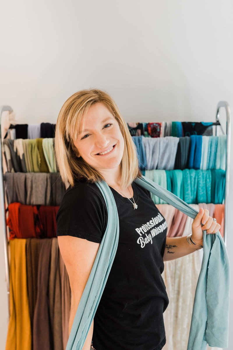 Kira Jeffrey posing in her portrait studio in front of colorful wraps for newborn portraits