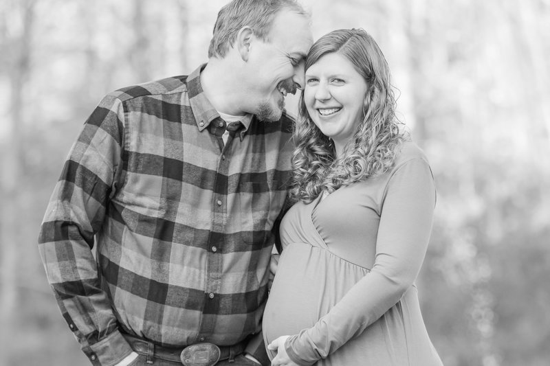 Husband and wife embrace and smile as wife hold her pregnant belly during maternity photo session