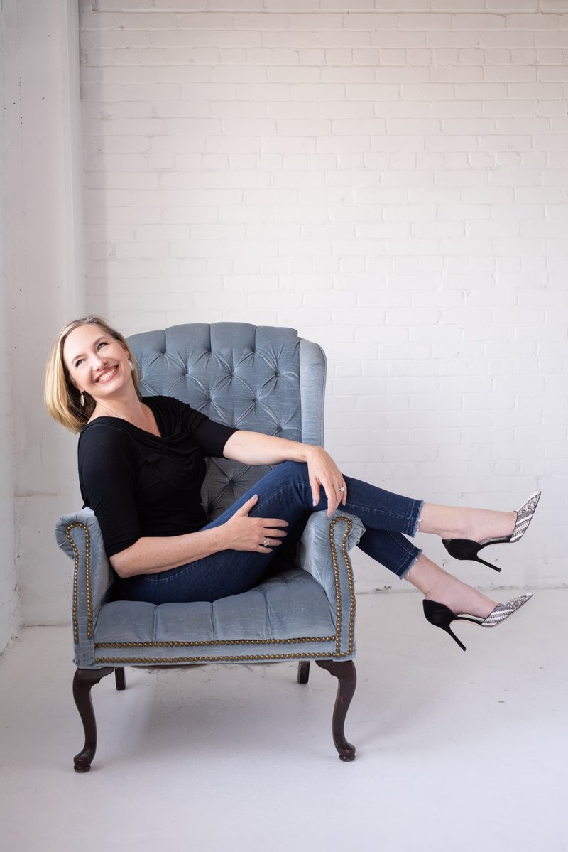 Headshot of Jen Denton sitting with high heels and smiling looking out a window