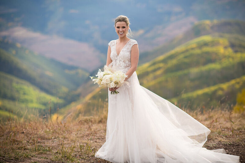 Testimonial photo, bride in flowing lace dress smiles at a camera with hills behind her