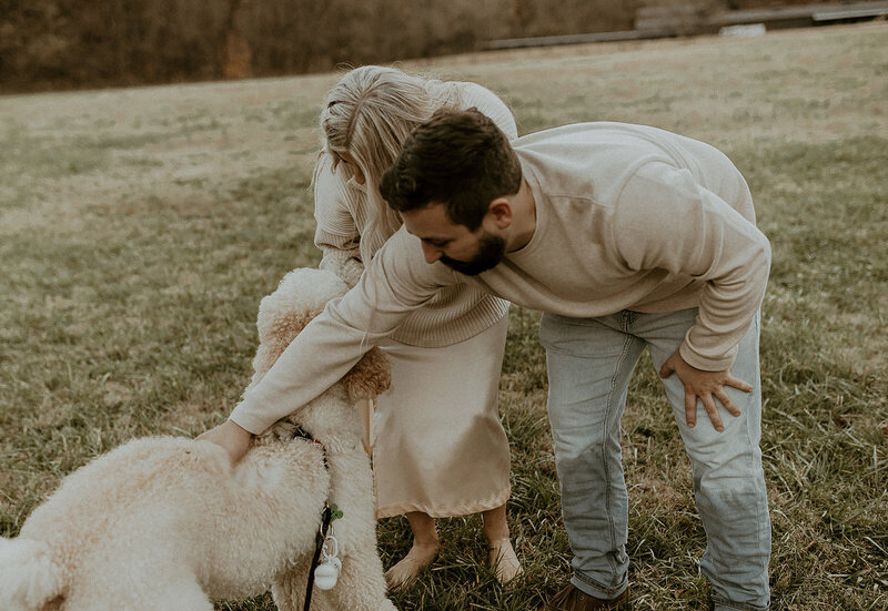 Couple petting Kylee's dog, Ozzy, during their engagement session