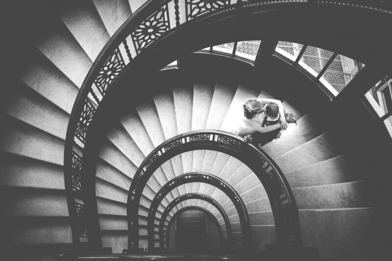 A timeless, black and white image of a bride and groom kissing on the spiral stairs of the Rookery Building in Chicago.