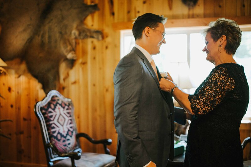 Gatlinburg Photographer Groom and his mother helping get ready before big nashville wedding in a log cabin in the woods