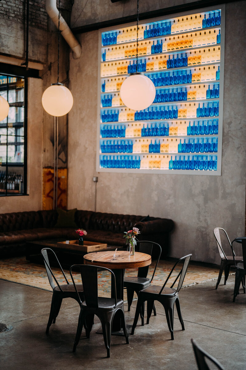 a small wooden circular table with metal chairs sits in front of a leather couch with  a heart made out of gin bottles on the wall in philadelphia distilling company shot by philadelphia wedding photographer alex medvick