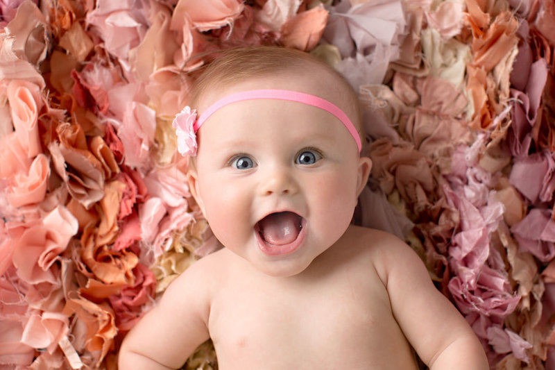 Baby girl smiles on pink colorful rug