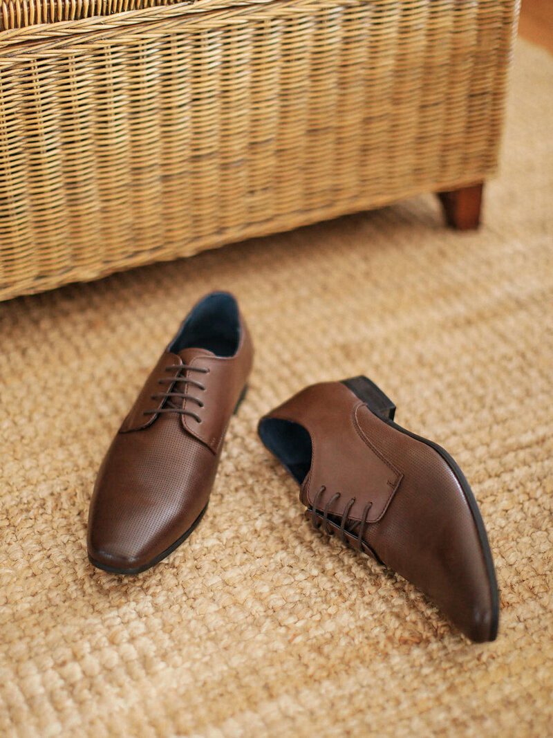Brown leather shoes on rug