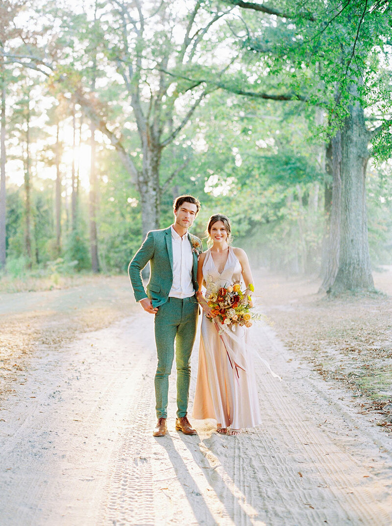 Apricot wedding dress and sage green groom suit during Golden Hour wedding portraits