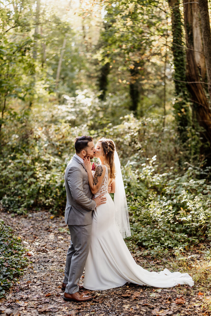 bride and groom kissing in woods