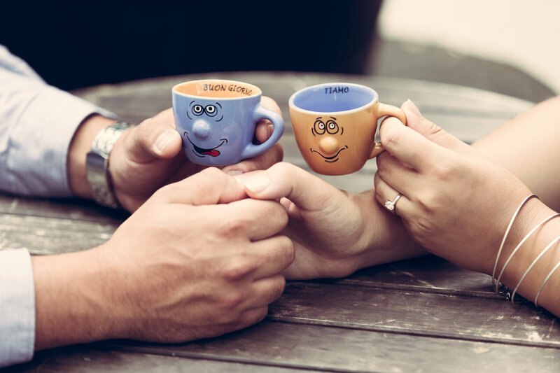 A close up photo of a bride and groom holding hands and espresso cups.