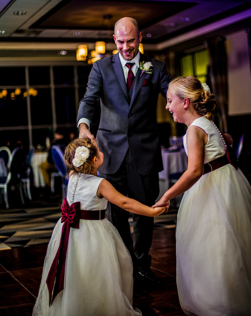 Flowergirls dancing with groomsman at Sheraton Erie Bayfront Hotel wedding reception