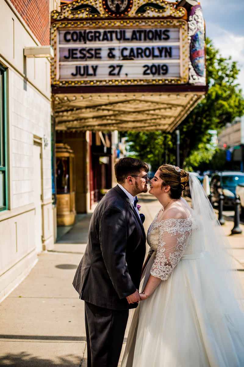 Bride and groom holding hands under the Warner Theatre marquee during the day