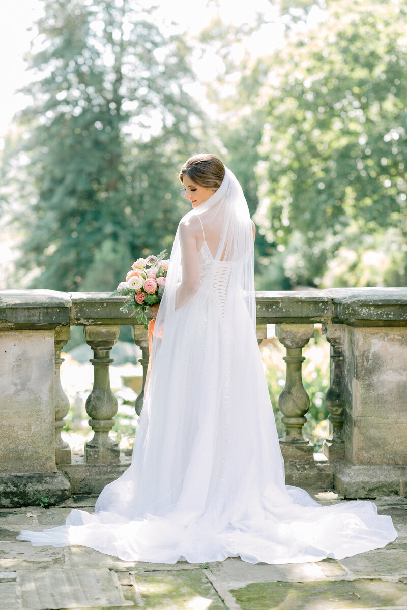 Virginia Wedding Photographer, bride standing next to stone railing