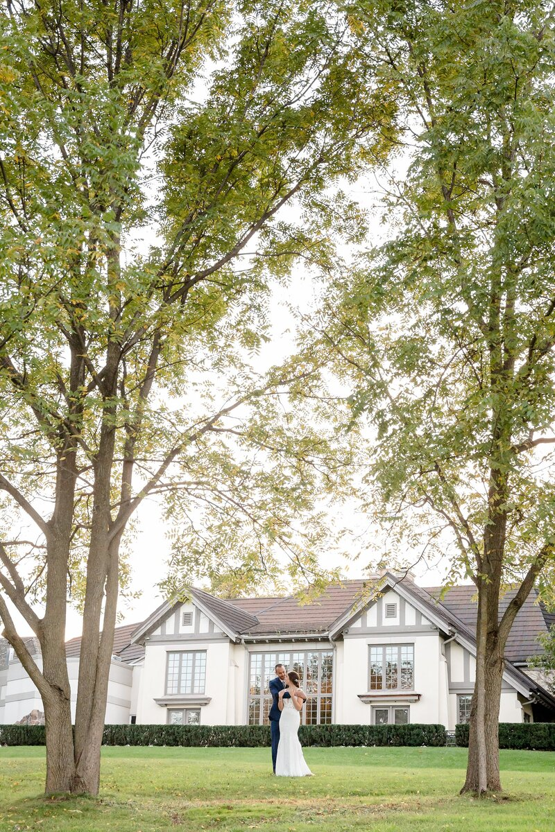 Groom embraces his bride under two large trees on the grounds of Windermere Manor in London Ontario