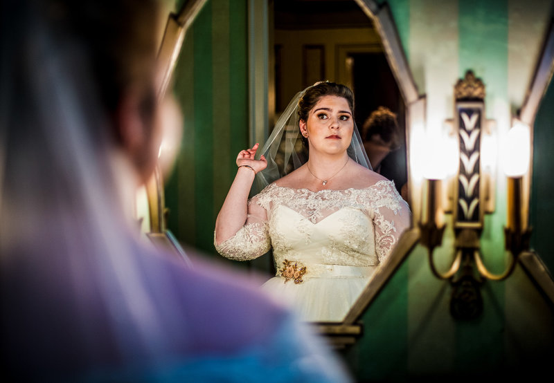 Bride adjusts veil in a mirror before her Warner Theatre wedding