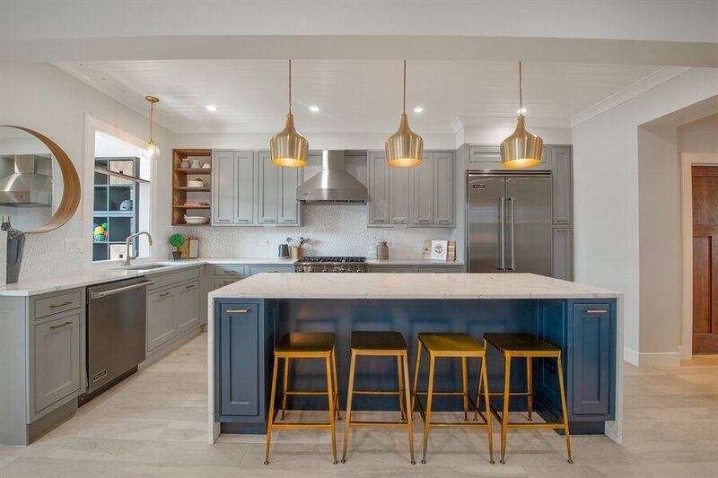 Blue Gold and White Kitchen with brass bar stools blue wood and white marble counter tops grey wood cabinets and stainless steel appliances