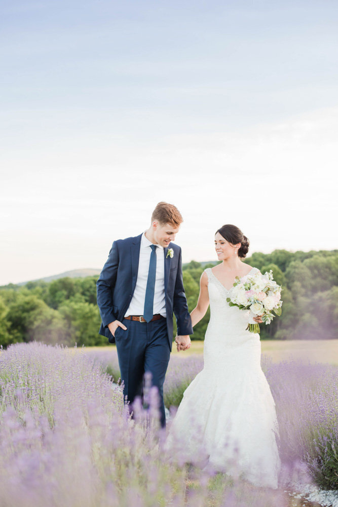 couple walking through lavender fields at springfield manor winery and distillery wedding by costola photography