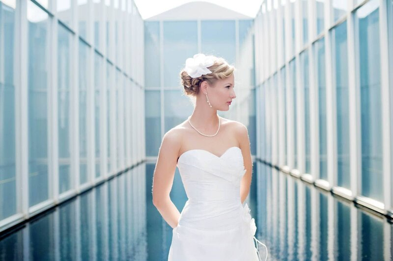 a pretty bride looks away standing in front of a bright blue reflection pool at an art museum