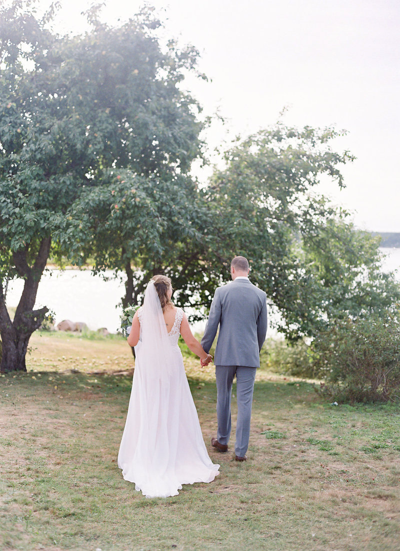Couple on their wedding day walking towards their ceremony location at Shining Waters Marina in the shadow of an Apple Tree