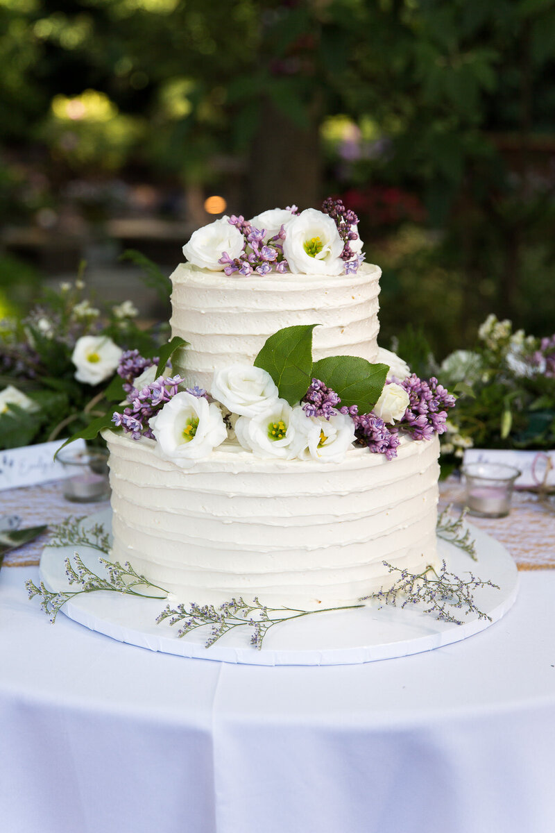 wedding cake with purple and white flowers