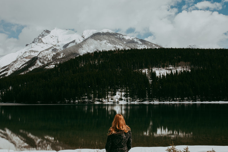 woman looking out over lake and mountains