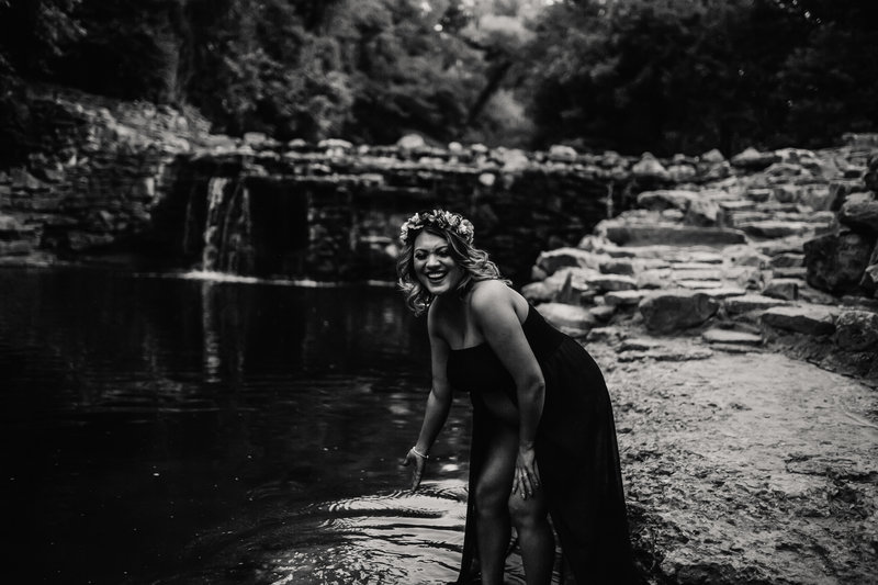 pregnant hispanic woman in black dress laughing while splashing water in a creek with a waterfall behind her