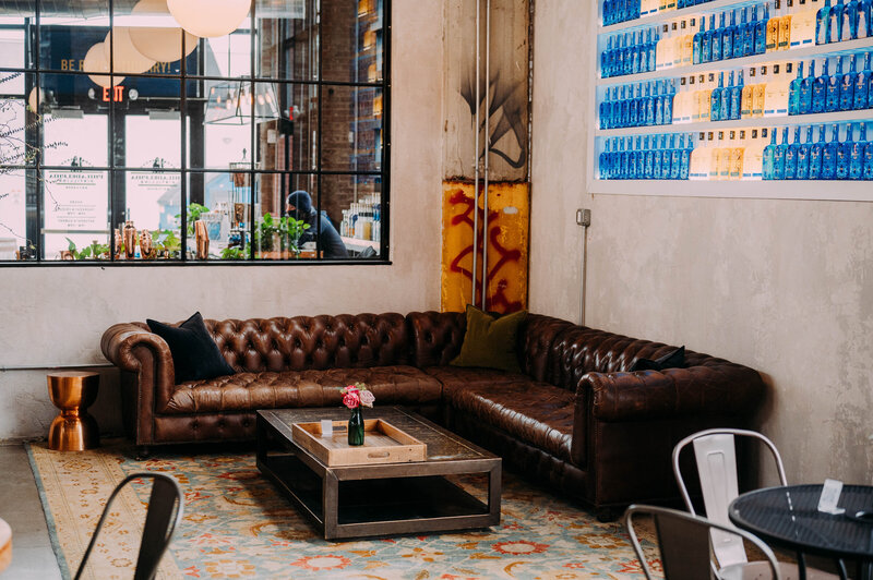 a leather couch sits in the corner of philadelphia distilling company shot by philadelphia wedding photographer alex medvick