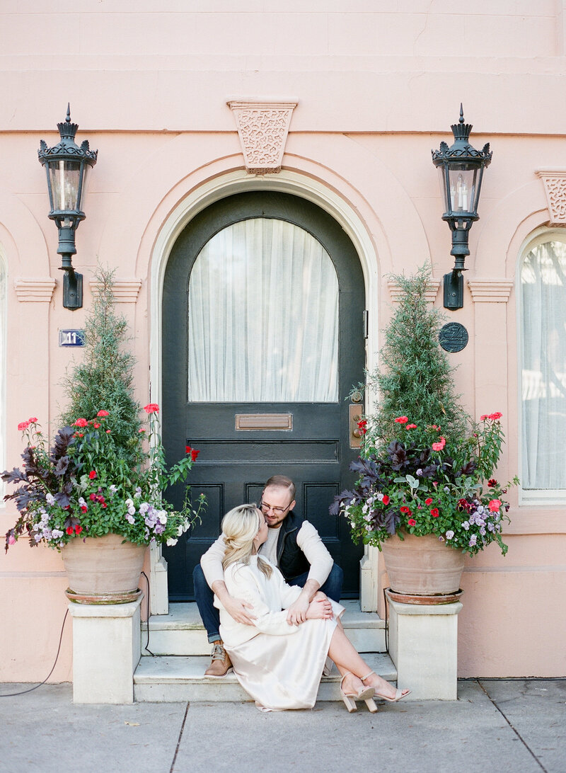 couple takes engagement photos in Charleston on steps, pink building and flowers