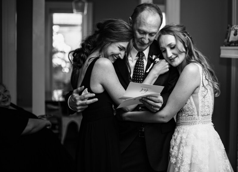 Bride hugging her sister and father before the ceremony