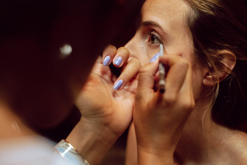 Detailed image of make-up artist putting on the brides eye liner